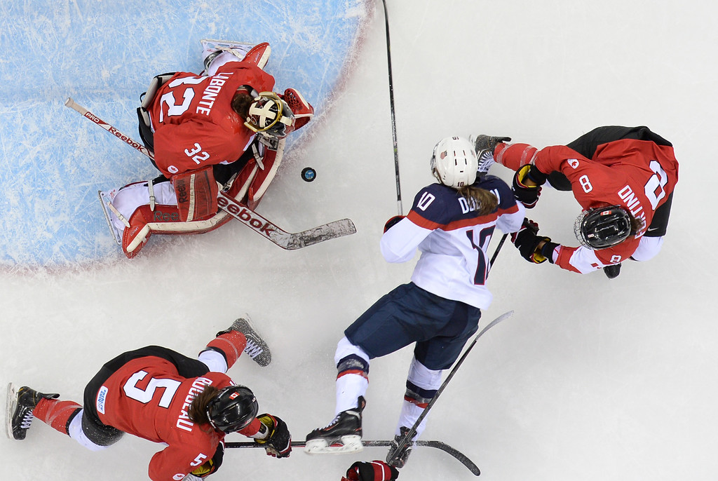 . US Jocelyne Lamoureux (C) vies for the puck with Canada\'s Laura Fortino (R) and goalkeeper Charline Labonte during the Women\'s Ice Hockey Group A match between Canada and USA at the Sochi Winter Olympics on February 12, 2014 at the Shayba Arena. AFP PHOTO / JONATHAN NACKSTRAND/AFP/Getty Images