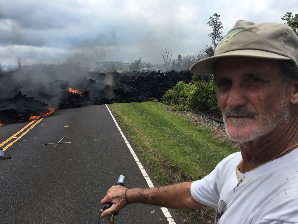 . Resident Sam Knox, 65, rides his bicycle to the edge of the road as lava burns across the road in the Leilani Estates in Pahoa, Hawaii, Saturday, May 5, 2018. Hundreds of anxious residents on the Big Island of Hawaii hunkered down Saturday for what could be weeks or months of upheaval as the dangers from an erupting Kilauea volcano continued to grow. Lava spurted from volcanic vents, toxic gas filled the air and strong earthquakes, including a magnitude 6.9 temblor on Friday, rocked an already jittery population. (AP Photo/Marco Garcia)