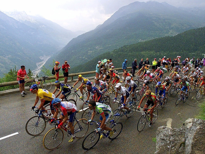 . Overall leader Lance Armstrong of the U.S., left in yellow, and the rest of the pack climb Tamie pass during the ninth stage of the Tour de France cycling race between Le Grand-Bornand, French Alps, and Sestrieres in the Italian Alps Tuesday, July 13, 1999. (AP Photo/Laurent Rebours)