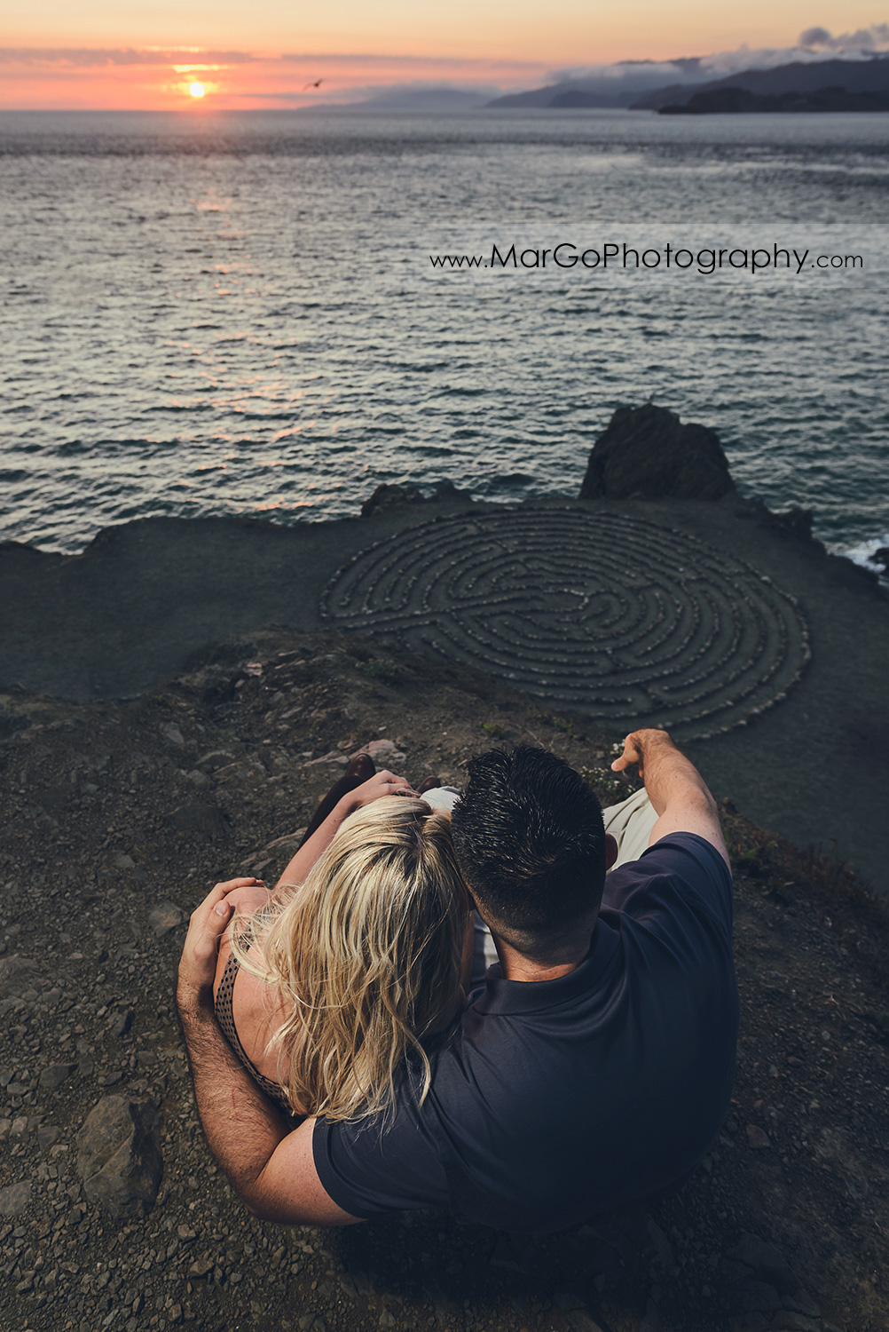 man in navy blue shirt and woman in brown tunic watching sunset above stone labyrinth during engagement session at San Francisco Lands End