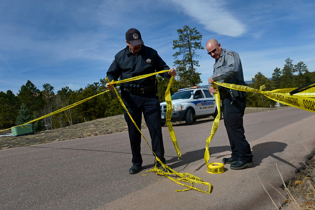 . El Paso County Sheriff\'s Deputies Larry Murphy, left, and Sean Ives, right, fix the police tape near the scene along the 17400 block of Colonial Park Drive. (Photo By Helen H. Richardson/ The Denver Post)