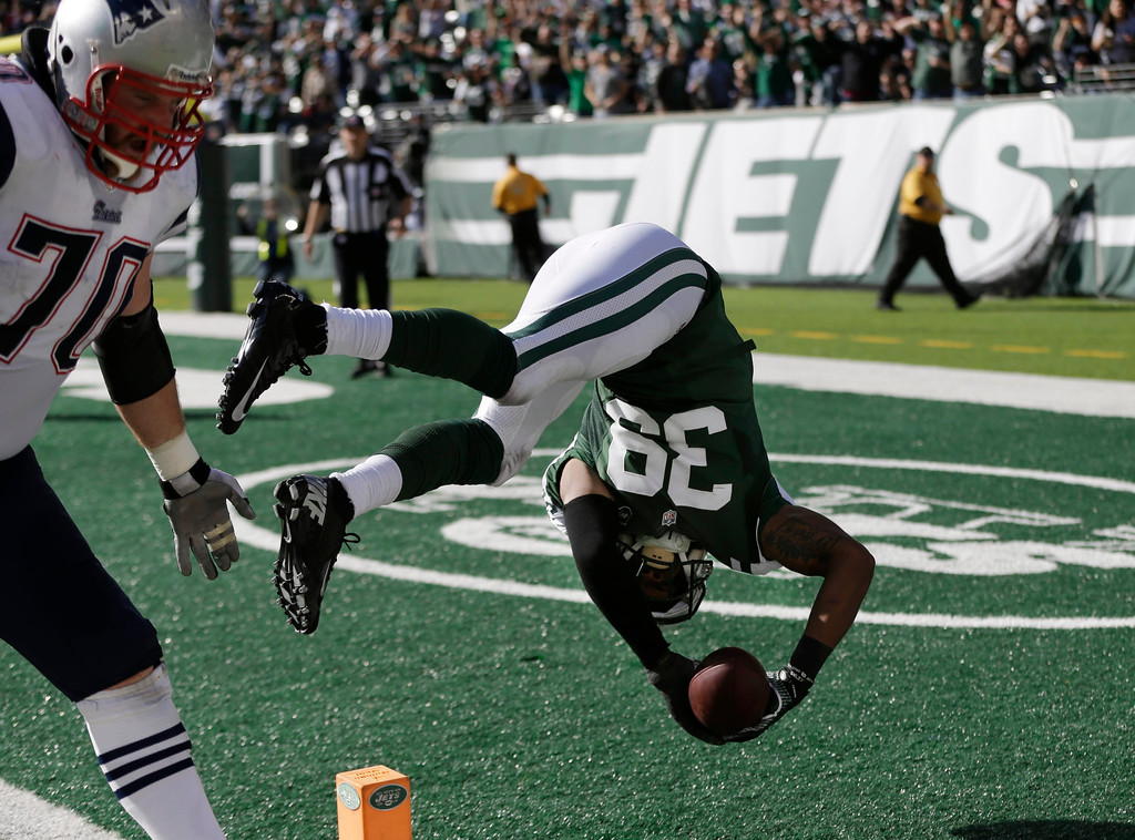. New York Jets free safety Antonio Allen (39) flips into the end zone for a touchdown after intercepting a pass by New England Patriots\' Tom Brady during the second half of an NFL football game Sunday, Oct. 20, 2013, in East Rutherford, N.J. New England Patriots\' Logan Mankins (70) trails the play. (AP Photo/Seth Wenig)