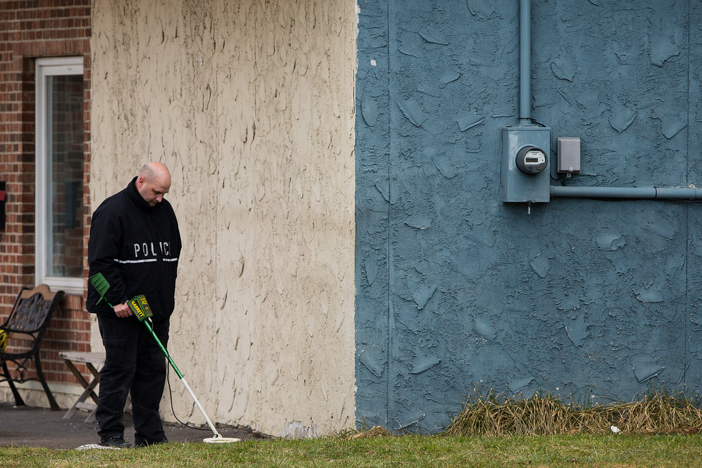 . A Police officer searches the area around Gaffey\'s Fast Lube and Car Wash where a gunman shot and killed two people on March 13, 2013 in Herkimer, New York. (Photo by Brett Carlsen/Getty Images)
