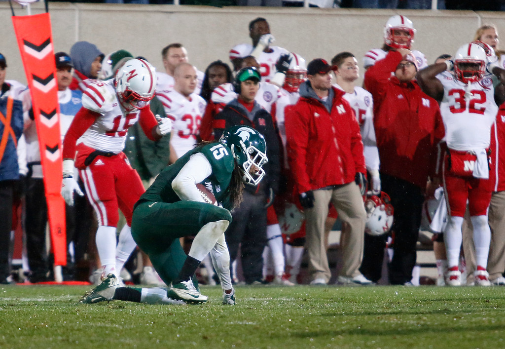 . Michigan State\'s Trae Waynes, center, kneels down after intercepting a pass intended for Nebraska\'s De\'Mornay Pierson-El, left, with less than a minute remaining in an NCAA college football game, Saturday, Oct. 4, 2014, in East Lansing, Mich. Michigan State won 27-22. (AP Photo/Al Goldis)