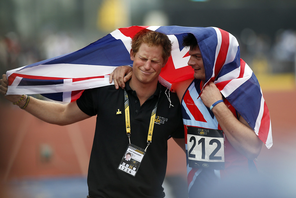 . Britain\'s Prince Harry (L) celebrates with Great Britain\'s David Henson after the latter won the 200m men ambulant IT2 race during the athletics event of the Invictus Games at Queen Elizabeth II Park in London on September 11, 2014. AFP PHOTO/ADRIAN DENNISADRIAN DENNIS/AFP/Getty Images