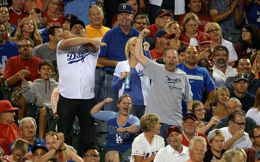 . Los Angeles Dodgers fans cheer after right fielder Yasiel Puig (not pictured) leaps to catch a drive by Los Angeles Angels\' Josh Hamilton (not pictured) in the sixth inning of a baseball game at Anaheim Stadium in Anaheim, Calif., on Thursday, Aug. 7, 2014.  (Photo by Keith Birmingham/ Pasadena Star-News)