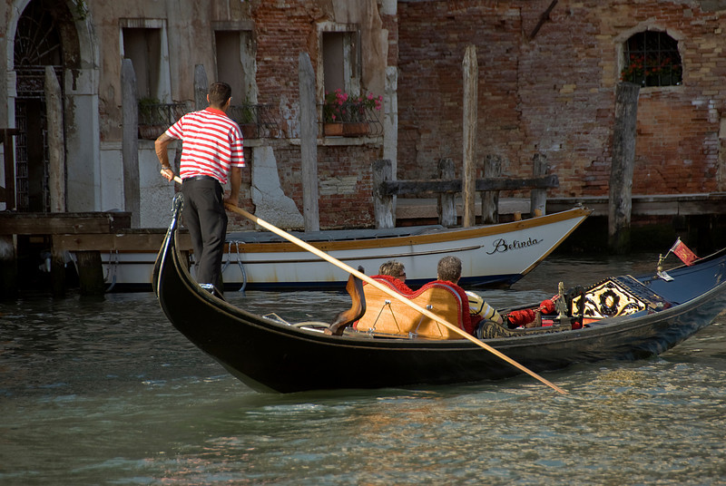 Tourists riding the gondola at sunset in Venice, Italy