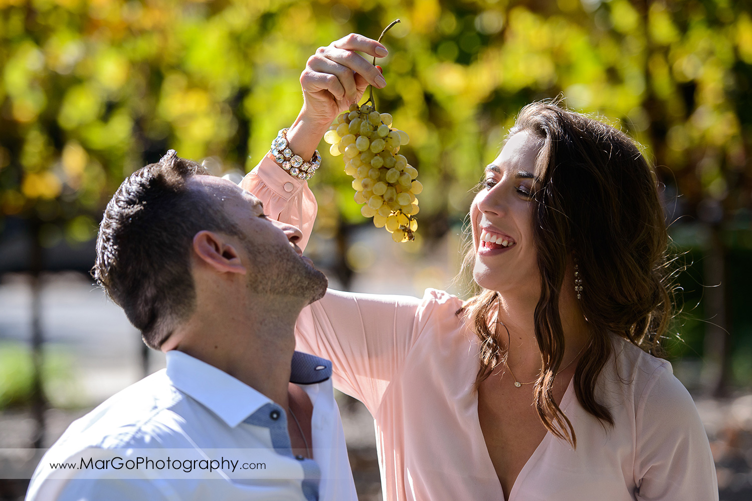 man in white shirt and woman in pink dress eating grapes during Napa Valley engagement session at Frank Family Vineyards in Calistoga