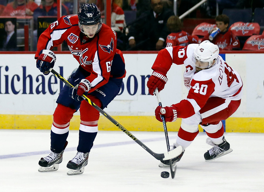 . Washington Capitals left wing Andre Burakovsky (65), from Austria, goes for the puck with Detroit Red Wings left wing Henrik Zetterberg (40), from Sweden, in the second period of an NHL hockey game, Wednesday, Oct. 29, 2014, in Washington. (AP Photo/Alex Brandon)