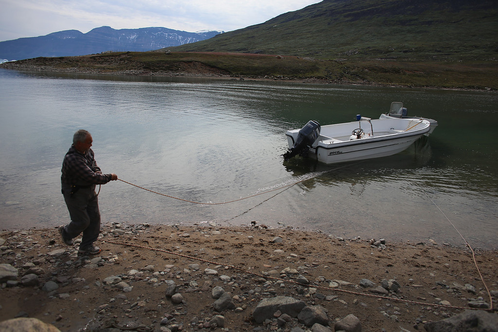. Potato farmer Ferdinan Egede ties up his boat which is the only mode of transportation on the isolated water front farm on July 31, 2013 in Qaqortoq, Greenland.  (Photo by Joe Raedle/Getty Images)