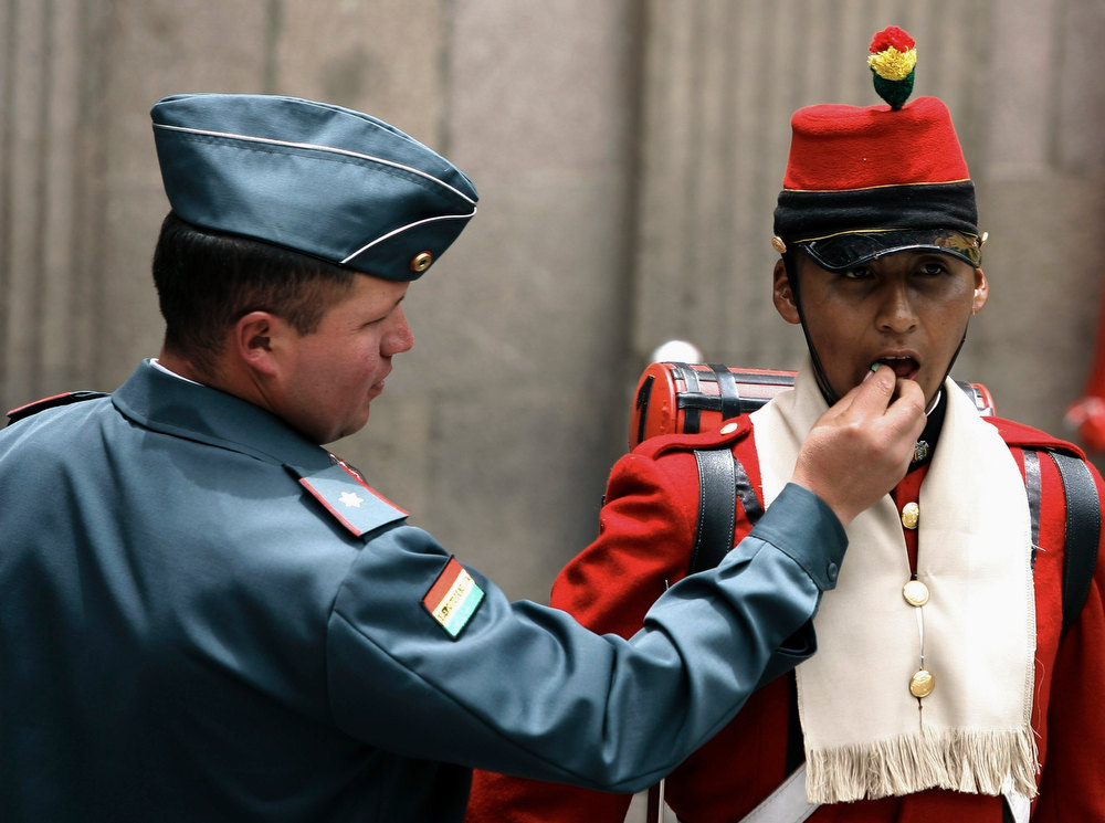 Description of . An army officer (L) puts a candy in the mouth of a Bolivia's Presidential guard member, who is standing at attention, during celebrations commemorating President Evo Morales' eighth continuous year of government, in La Paz January 22, 2013. Morales, Bolivia's first indigenous president, took office on January 22, 2006, after winning the presidential election with 53.7% and he was re-elected for a second term on 2010-2015 with 64% of the votes according local media. REUTERS/Gaston Brito