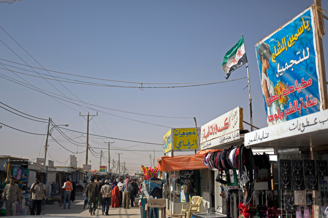 """. In this Thursday April 17, 2014 photo, Syrian refugees walk on the market street at Zaatari refugee camp, near the Syrian border in Jordan. A Syrian revolution flag flies above one shop, between banners with Arabic writing that read \""""Yasmeen al-Sham for Beauty,\"""" \""""Al-Mahabba accessories shop,\"""" and \""""Al-Refaey Jewelry shop.\"""" (AP Photo/Khalil Hamra)"""