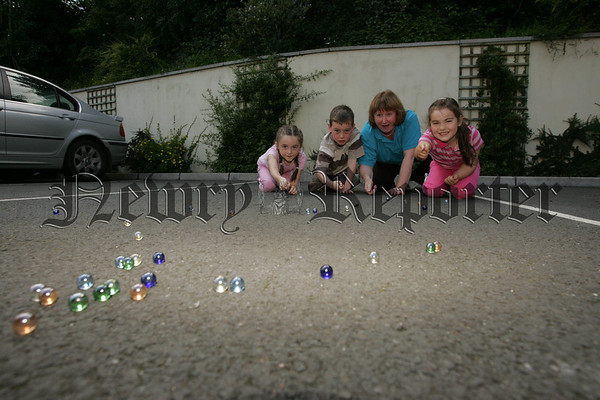 Annie Loughran, Michael McKenna and Cliodhna Bradley enjoy a game of marbles with Mary Hull from Surestart. 07W30N23