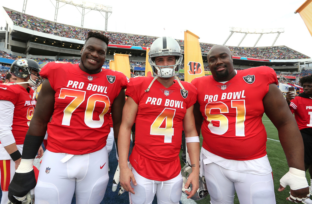 . From left to right, AFC offensive guard Kelechi Osmele, AFC quarterback Derek Carr, and AFC center Rodney Hudson, all of the Oakland Raiders, pose for photo prior to the NFL Pro Bowl football game at Camping World Stadium, Sunday, Jan. 28, 2018, in Orlando, Fla. (AP Photo/Doug Benc)