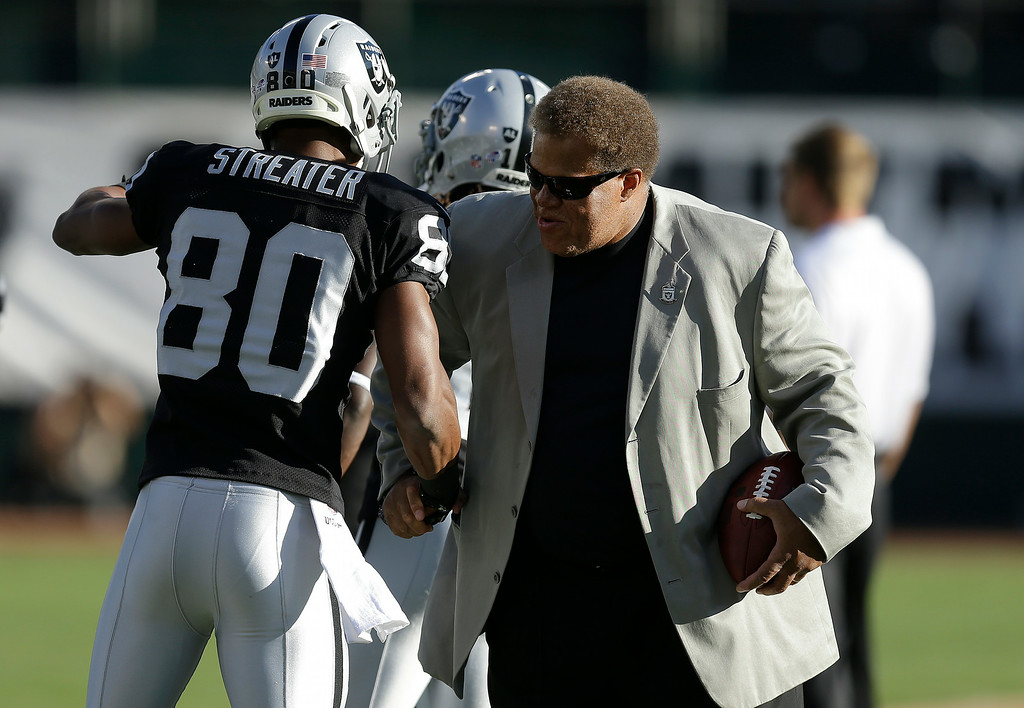 . Oakland Raiders wide receiver Rod Streater (80) shakes hands with general manager Reggie McKenzie before an NFL preseason football game against the Detroit Lions in Oakland, Calif., Friday, Aug. 15, 2014. (AP Photo/Ben Margot)