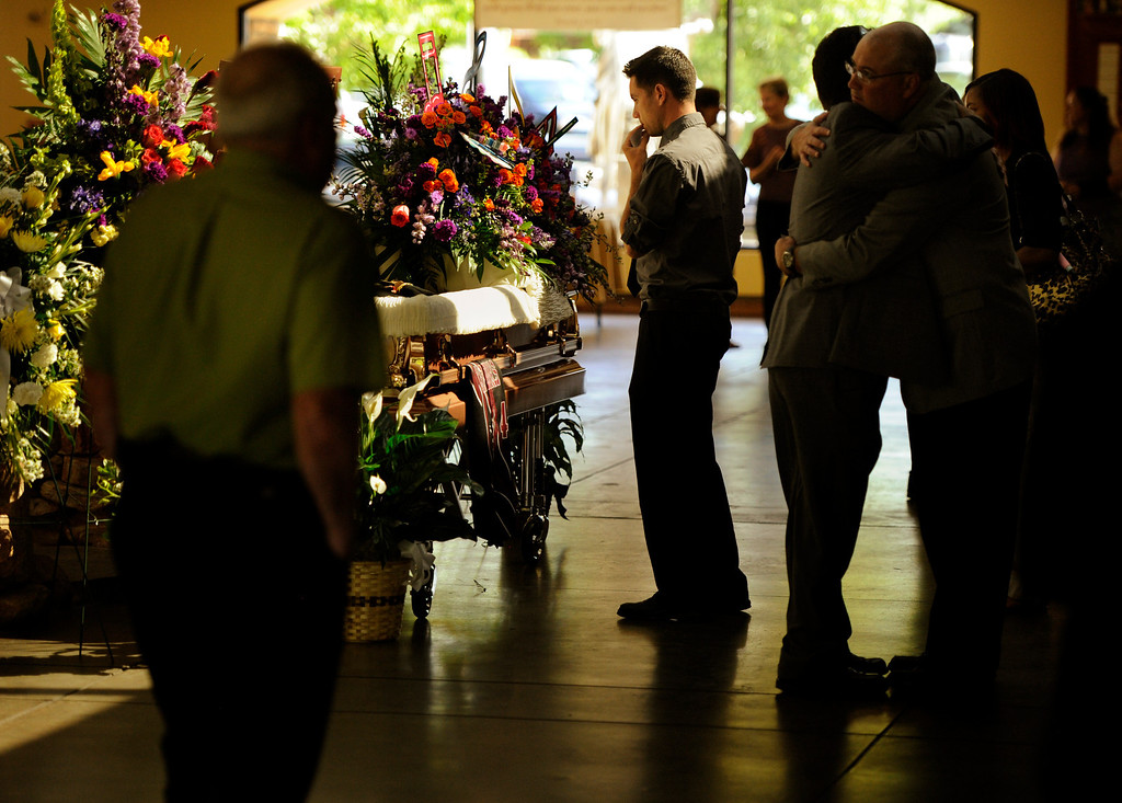 . A young man pays his respects during the final viewing at the funeral for AJ Boik Friday, July 27, 2012 at the Queen of Peace Catholic Church in Aurora. Joe Amon, The Denver Post