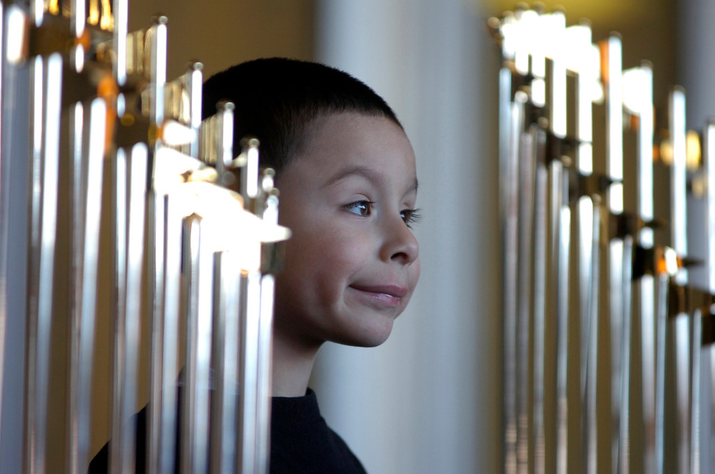 . Juan Pena, 4, of San Francisco, smiles as he is photographed with the World Series Trophy as it makes a stop at the Richmond Memorial Auditorium in Richmond, Calif. on Monday, Jan. 14, 2013.  (Kristopher Skinner/Staff)