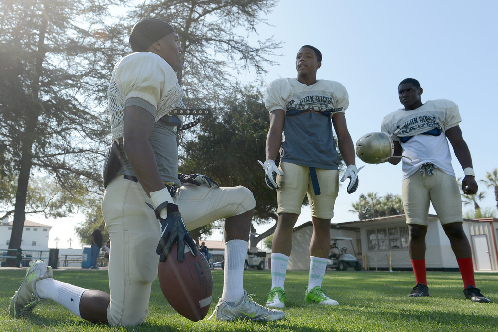 . St. John Bosco\'s Najiel Hale,center, talks to Jaleel Wadood, left, as the two take a breather during a practice as the team prepares for the 2013 season in Bellflower August 14, 2013.  (Thomas R. Cordova/Staff Photographer)