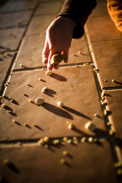 Child's hand picking up pebbles from the floor, Seville, Spain
