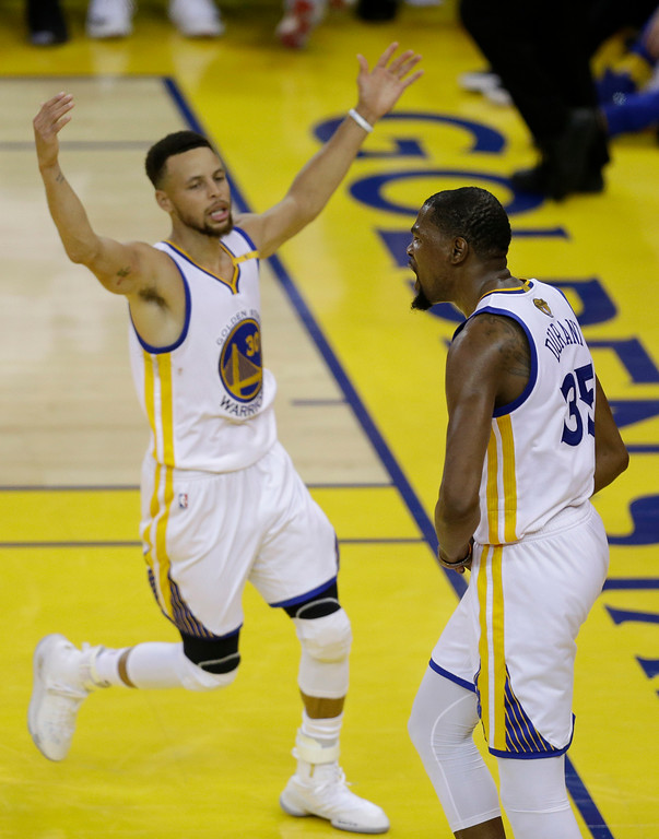 . Golden State Warriors forward Kevin Durant, right, and guard Stephen Curry (30) celebrate during the second half of Game 2 of basketball\'s NBA Finals against the Cleveland Cavaliers in Oakland, Calif., Sunday, June 4, 2017. (AP Photo/Ben Margot)