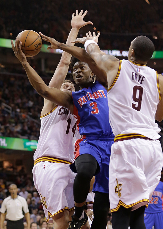 . Detroit Pistons\' Stanley Johnson (3) drives between Cleveland Cavaliers\' Sasha Kaun (14), from Russia, and Channing Frye (9) during the second half of an NBA basketball game Wednesday, April 13, 2016, in Cleveland. The Pistons won 112-110. (AP Photo/Tony Dejak)