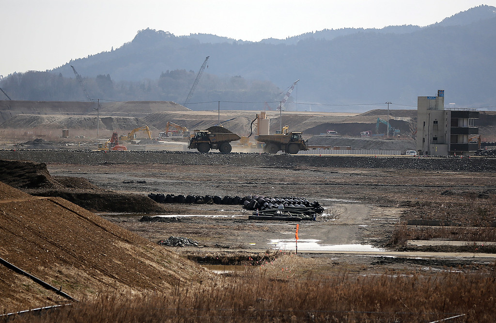 . In this Friday, March 6, 2015 photo, trucks carry soil to the Tsunami damaged area in Rikuzentakata, Iwate Prefecture, northeastern Japan. Still struggling to recover, the tsunami-hit region of northeastern Japan marks the fourth anniversary of the March 11, 2011, disaster Wednesday. (AP Photo/Eugene Hoshiko)