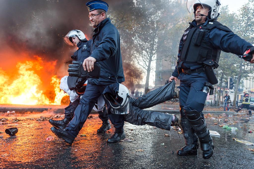 . Policemen carry an arrested protestor , during a national trade union demonstration in Brussels, Thursday Nov. 6, 2014. (AP Photo/Geert Vanden Wijngaert)