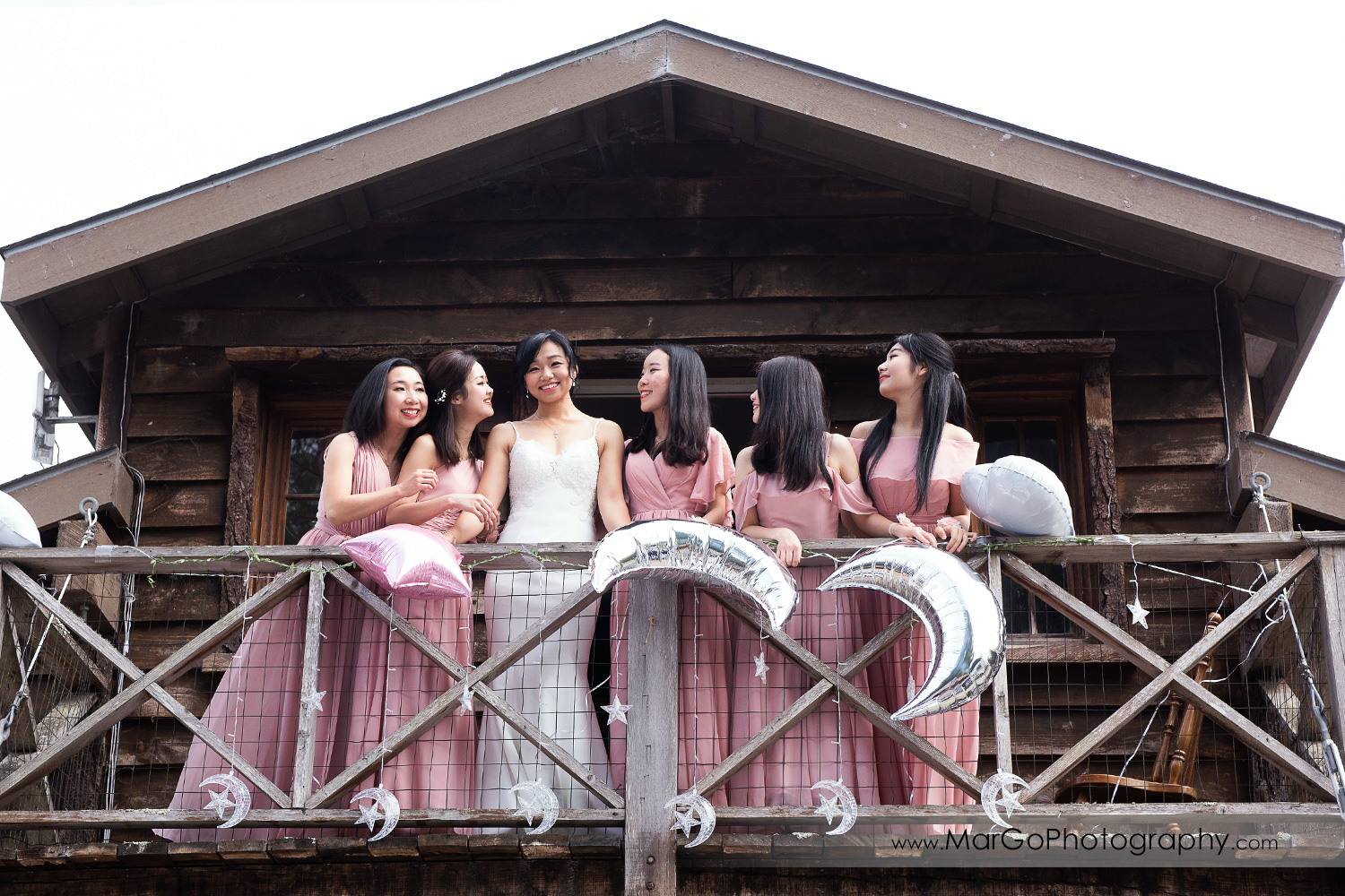 bride in white dress and bridesmaids in pink dresses on balcony at Long Branch Saloon & Farms in Half Moon Bay