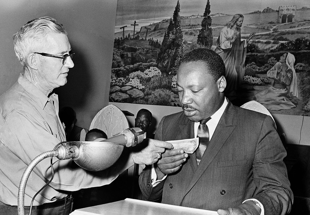 ". Dr. Martin Luther King Jr. (right) who is visiting Mississippi to drum up funds his Poor Peoples March 19, 1968 in Marks, Mississippi USA.  King holds a crisp $100 bill and listens to remarks by a  Marks, Mississippi, resident , at left, who identified himself as W.B. ""Money\"" Mobley.   Mr Mobley pushed his way through a crowd of several hundred and interrupted King\'s speech to present the $100 donation and asked for the floor.     Dr. King obliged. (AP Photo/Jack Thornell)"