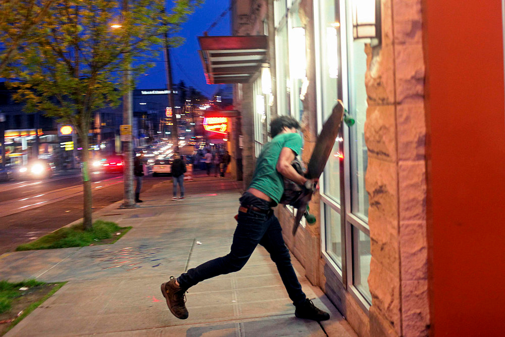 . A demonstrator attempts to break a window of a pharmacy on Capitol Hill during May Day demonstrations in Seattle, Washington May 1, 2013. Protesters clashed with police in Seattle on Wednesday as a May Day rally that began peacefully turned violent after dark, with demonstrators hurling objects at officers who responded by firing flash-bang grenades and pepper spray.     REUTERS/Matt Mills McKnight