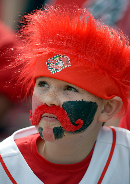 . Max Tramontana, 10, watches batting practice prior to a baseball game between the Cincinnati Reds and the St. Louis Cardinals, Monday, March 31, 2014, on opening day in Cincinnati. (AP Photo/Michael Keating)