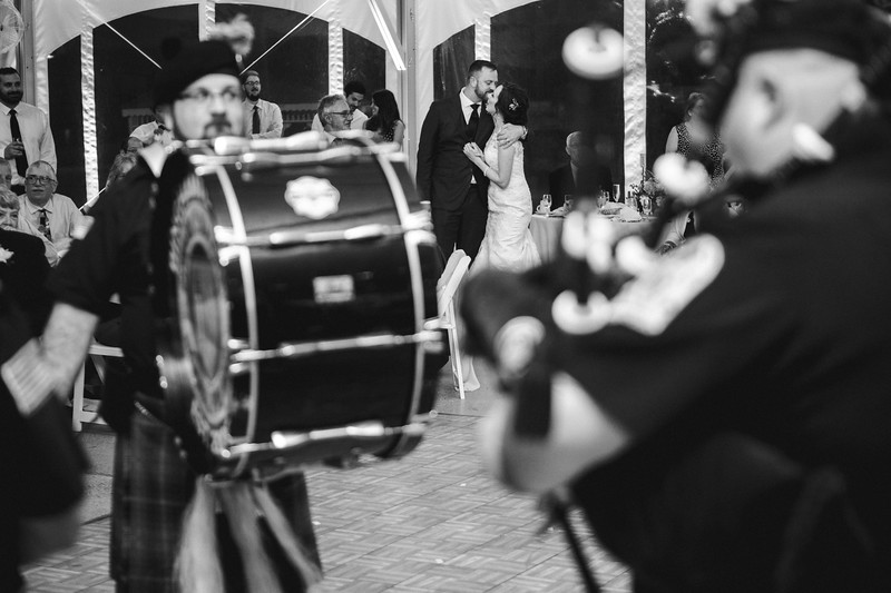 The bride and groom kiss as the bag pipers perform.