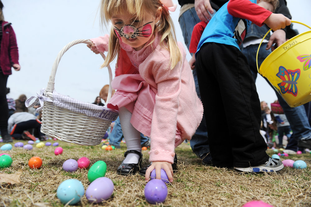 . Heidi Giannini, 4, picks up eggs and put them in her basket during the 66th annual West Side Nut Club Easter Egg Hunt  at Mater Dei High School on  Saturday, March 30, 2013 In Evansville, Ind. Children from pre-school to third grade collected more than 12,000 easter eggs filled with candy and prizes in less than a minute. (AP Photo/ The Courier & Press, Erin McCracken)