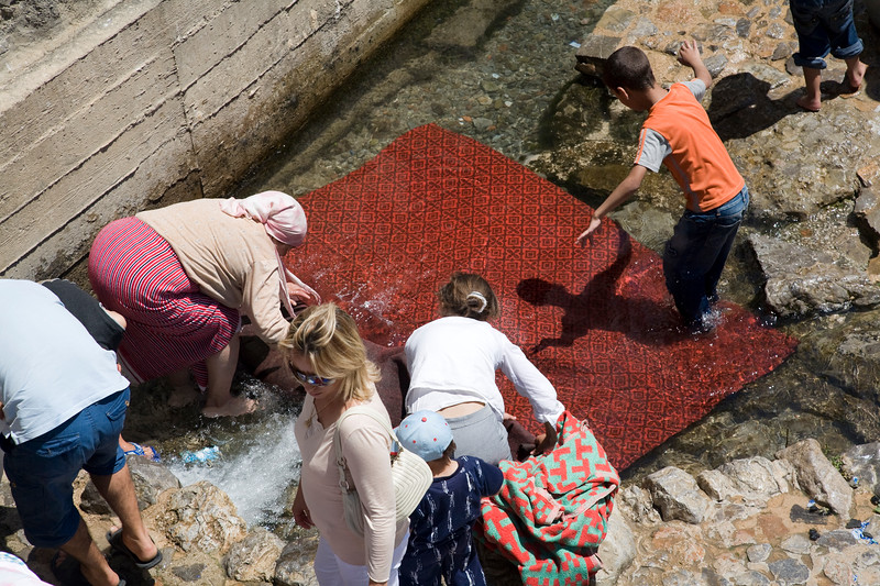 Women and kids washing carpets and blankets in a public washing place by the river, Chefchaouen, Morocco