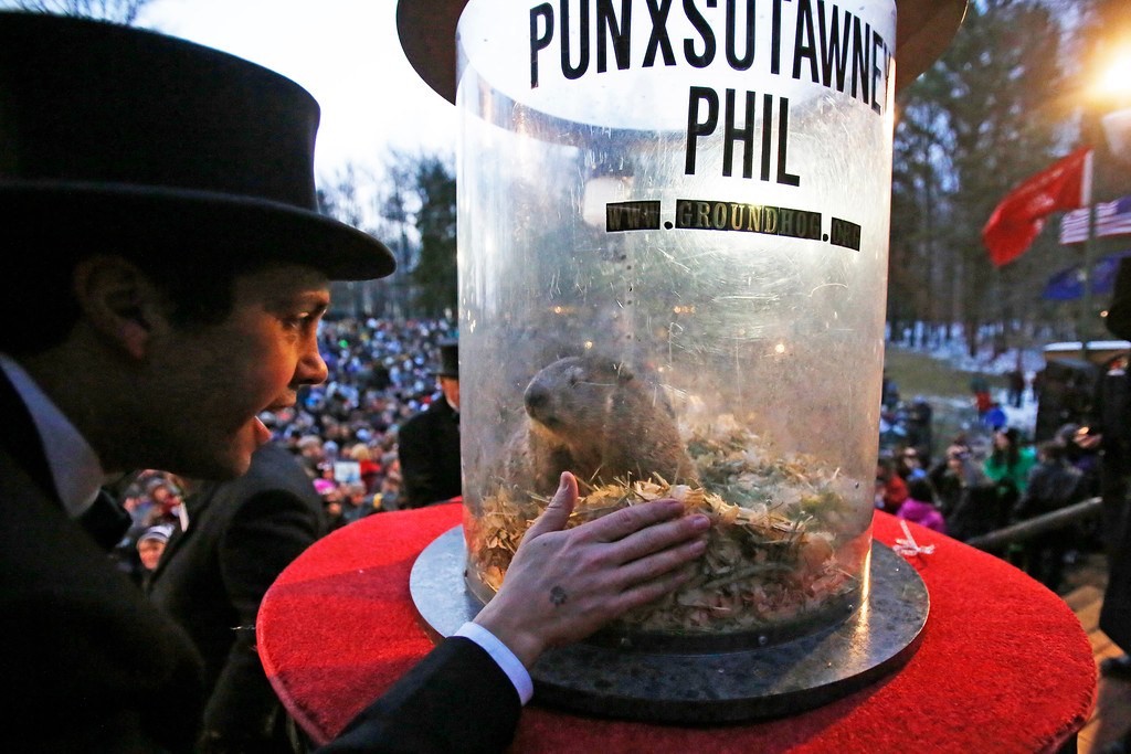 . Groundhog Club inner circle member Dan McGinley, left, visits with Punxsutawney Phil, the weather prognosticating groundhog, during the 131st celebration of Groundhog Day on Gobbler\'s Knob in Punxsutawney, Pa., Thursday, Feb. 2, 2017. Phil\'s handlers said that the groundhog has forecast six more weeks of winter weather. (AP Photo/Gene J. Puskar)