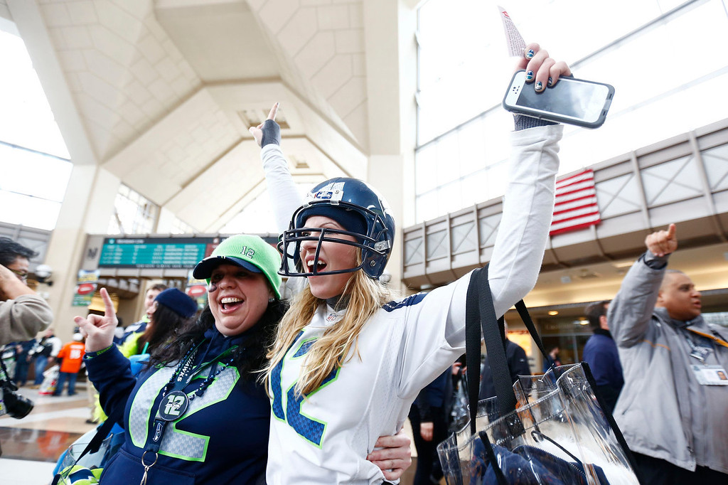. Football fans cheer at the Secaucus Junction, Sunday, Feb. 2, 2014, in Secaucus, N.J. The Seattle Seahawks are scheduled to play the Denver Broncos in the NFL Super Bowl XLVIII football game on Sunday evening at MetLife Stadium in East Rutherford, N.J. (AP Photo/Matt Rourke)