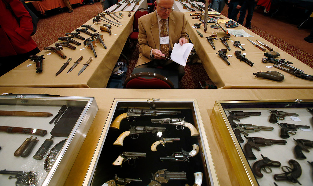 . Antique gun collector Dave Kleiner reviews paperwork during the East Coast Fine Arms Show in Stamford, Connecticut, January 5, 2013. REUTERS/Carlo Allegri