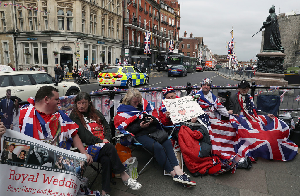. Royal fans John Loughry, second right, and Terry Hutt, center, show off their placards as TV and journalists film and interview them in just outside Windsor Castle, in Windsor, England, Wednesday, May 16, 2018. Preparations continue in Windsor ahead of the royal wedding of Britain\'s Prince Harry and Meghan Markle Saturday May 19, which includes a 30 minute carriage route taking the couple round the town to wave to the crowds, some of whom are already taking up positions . (AP Photo/Alastair Grant)
