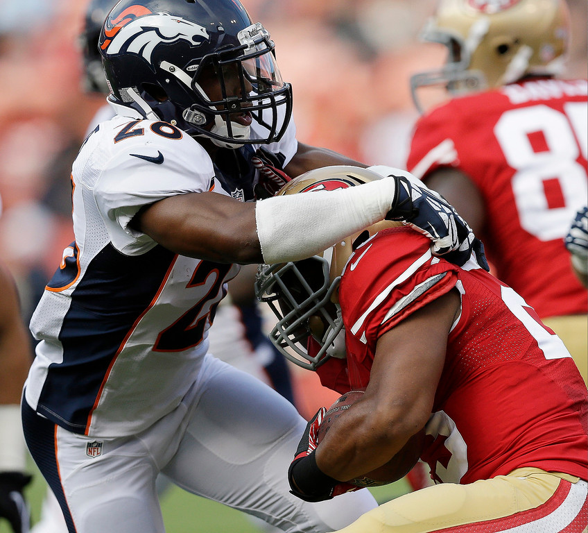 . San Francisco 49ers running back LaMichael James, right, is brought down with the ball by Denver Broncos free safety Rahim Moore, left, during the first quarter of an NFL preseason football game on Thursday, Aug. 8, 2013, in San Francisco. (AP Photo/Marcio Jose Sanchez)