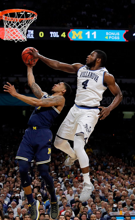. Villanova\'s Eric Paschall (4) blocks a shot by Michigan\'s Charles Matthews (1) during the first half in the championship game of the Final Four NCAA college basketball tournament, Monday, April 2, 2018, in San Antonio. (AP Photo/David J. Phillip)