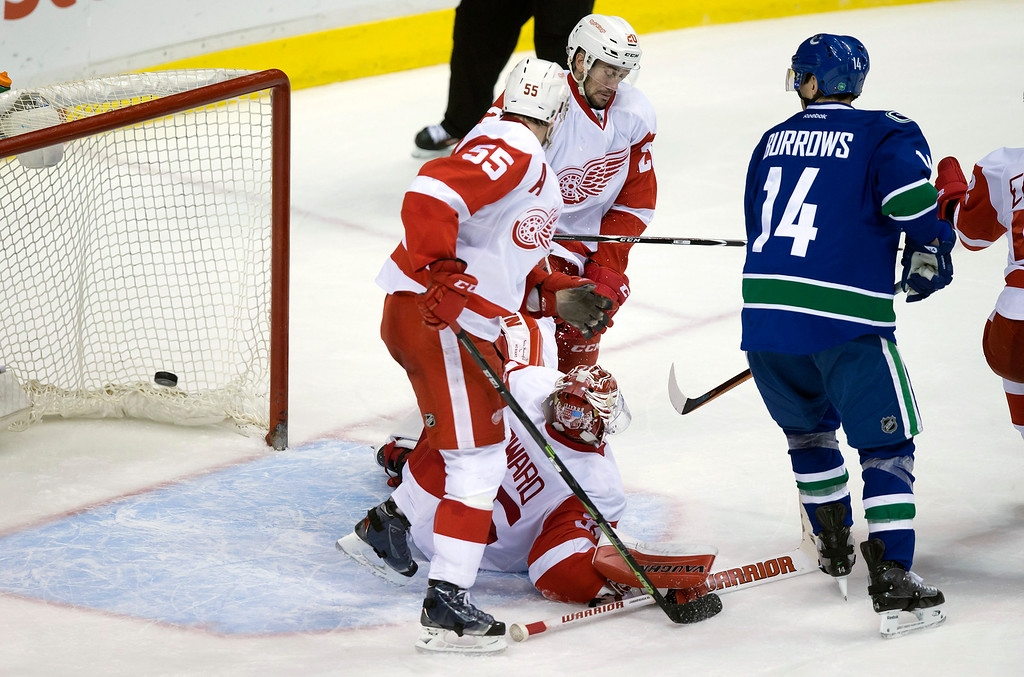 . Vancouver Canucks\' Alex Burrows, right, watches as a shot by teammate Radim Vrbata gets past Detroit Red Wings goalie Jimmy Howard, bottom, Niklas Kronwall, of Sweden, (55) and Drew Miller (20) for a goal during the third period of an NHL hockey game in Vancouver, British Columbia on Saturday, Jan. 3, 2015. (AP Photo/The Canadian Press, Darryl Dyck)