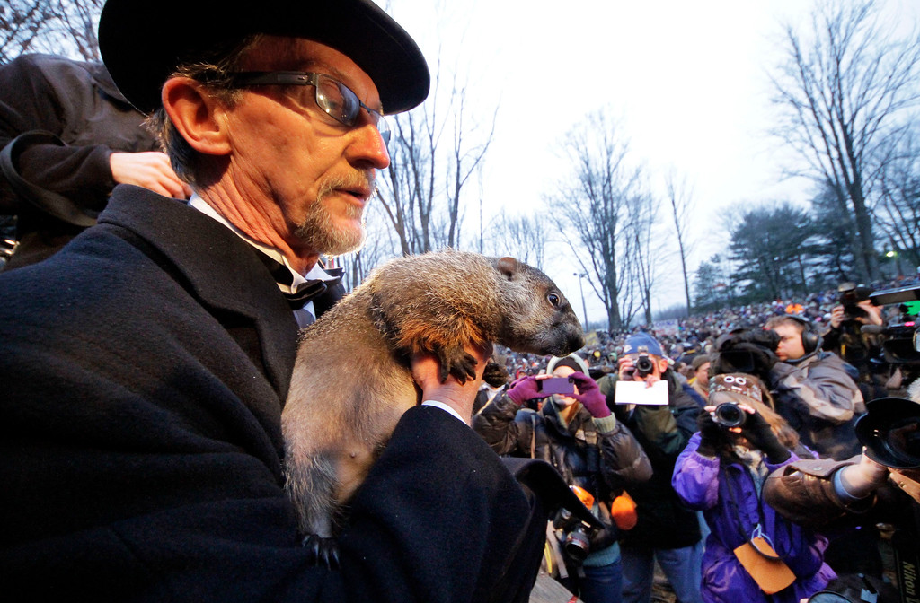 . FILE - In this Feb. 2, 2012 file photo, Groundhog Club handler Ron Ploucha holds Punxsutawney Phil, the weather prognosticating groundhog, during the 126th celebration of Groundhog Day on Gobbler\'s Knob in Punxsutawney, Pa. Groundhog Day is Saturday, and the community is holding its welcome-back bash for the famous winter-weather prognosticator _ the so-called seer of seers and sage of sages. Legend has it that if the groundhog sees his shadow on Feb. 2, winter will last six more weeks. No shadow means an early spring. (AP Photo/Gene J. Puskar, File)