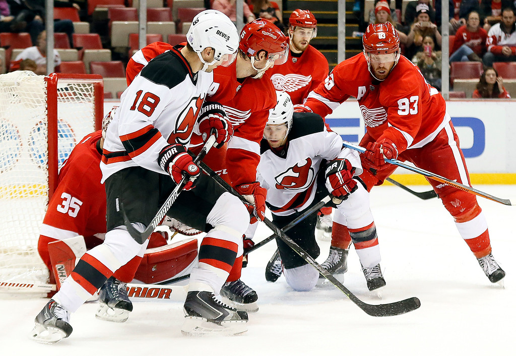 . Detroit Red Wings left wing Johan Franzen (93) checks New Jersey Devils center Travis Zajac (19) to the ice to prevent a shot in the third period of an NHL hockey game in Detroit, Friday, Nov. 7, 2014. Detroit won 4-2. (AP Photo/Paul Sancya)