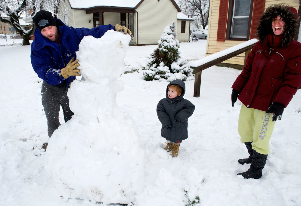 Description of . As blizzard conditions move through Henderson, Ky., Wednesday, Dec. 26, 2012 Joe Carroll (L) puts the head on a snowman as Isaiah Ross, 2 years-old, and Sherri Carroll watch in front of their home on 5th Street. (AP Photo/The Gleaner, Mike Lawrence)