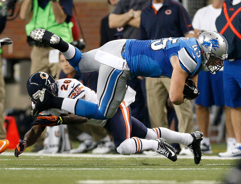 . Shaun Chapas #45 of the Detroit Lions is tackled by Tim Jennings #26 of the Chicago Bears after a first quarter catch at Ford Field on December 30, 2012 in Detroit, Michigan. (Photo by Gregory Shamus/Getty Images)