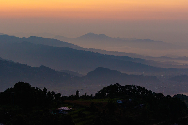 The sky turns orange as distant silhouetted hills come interview in Pokhara, Nepal - Sarangkot Road, Pokhara, Western Development Region, Nepal (NP)