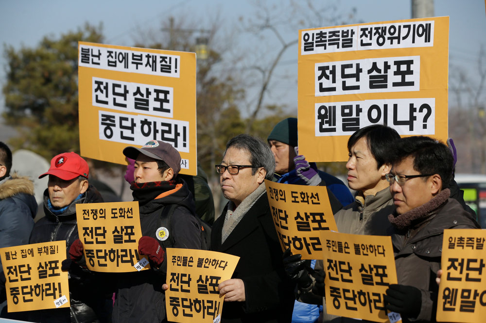 Description of . South Korean peace activists hold banners during a rally against anti-activists who send the leaflets at the Imjingak Pavilion near the border village of Panmunjom, in Paju, north of Seoul, South Korea, Saturday, Feb. 16, 2013. North Korean defectors and activists released 200,000 propaganda leaflets across the border to denounce the North Korea's third nuclear test and late leader Kim Jong Il's birthday on Saturday. The letters read;
