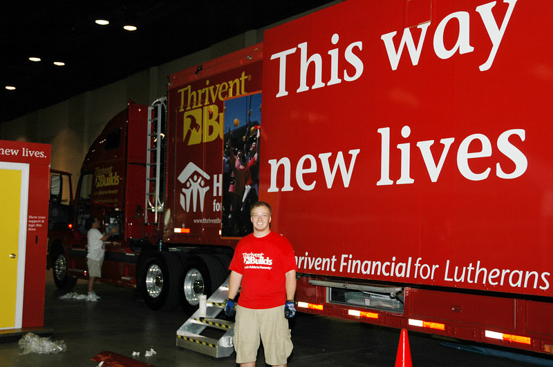 "Charles Boltas stands in front of the Thrivent Financial for Lutherans' ""Thrivent Builds Mobile."" Visitors to ""El Puente"" can tour the trailer and learn about what Thrivent is doing for communities in need."