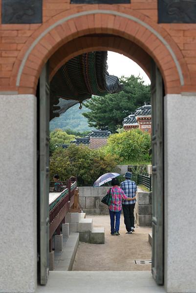Tourist in palace seen through an arch, Gyeongbokgung Palace, Seoul, South Korea