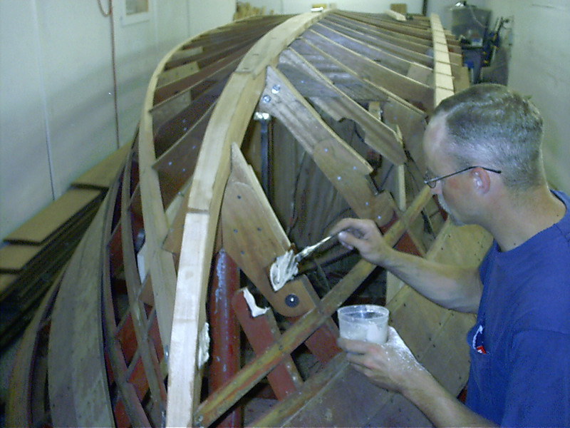 Applying epoxy to the boat before the chine is installed.